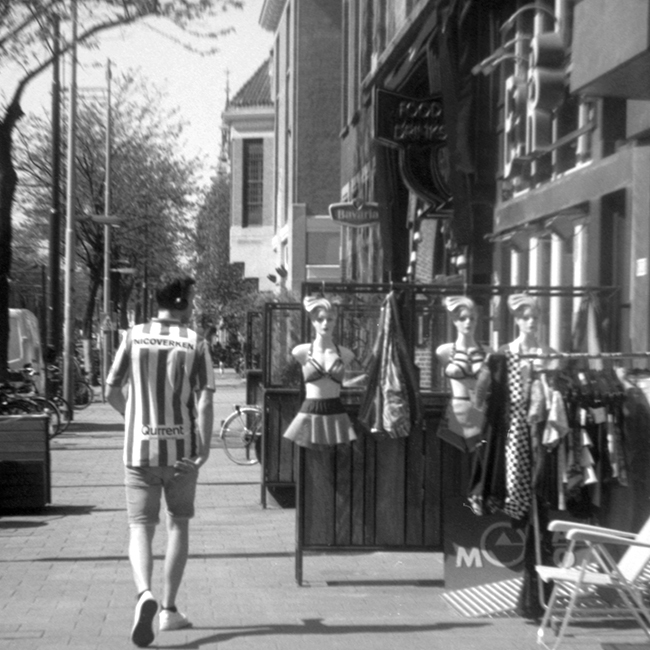 My beautiful stranger, black and white picture of man walking the street meeting mannequins